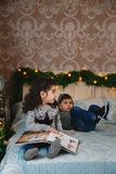 Portrait de Noël de petits enfants s'asseyant sur le lit avec des présents sous l'arbre de Noël et ayant l'amusement Noël de vaca Photos stock