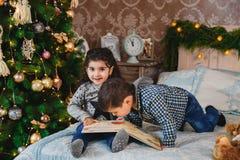 Portrait de Noël de petits enfants de sourire s'asseyant sur le lit avec des présents sous l'arbre de Noël Noël de vacances d'hiv Image libre de droits
