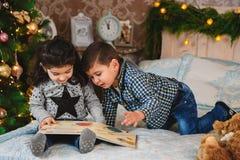 Portrait de Noël de petits enfants de sourire s'asseyant sur le lit avec des présents sous l'arbre de Noël Noël de vacances d'hiv Images libres de droits