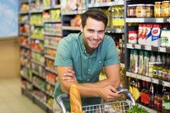 Portrait de nourriture de sourire et d'à l'aide d'achat d'homme de son smartphone Photographie stock libre de droits