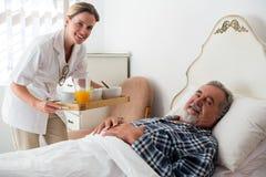 Portrait de nourriture femelle de portion de docteur au patient supérieur détendant sur le lit photos libres de droits