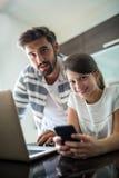Portrait de père et de fille à l'aide de l'ordinateur portable et du téléphone portable dans le salon Photos stock