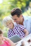 Portrait de père et de fils à l'aide du comprimé Photographie stock