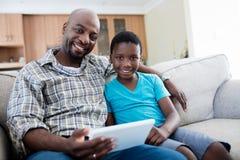 Portrait de père et de fils à l'aide du comprimé numérique dans le salon Image libre de droits