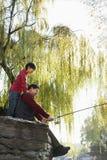 Portrait de pêche de grand-père et de petit-fils au lac Images stock