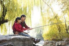 Portrait de pêche de grand-père et de petit-fils au lac Image stock