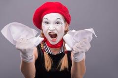 Portrait de pantomime femelle fâché chiffonnant un papier Image stock