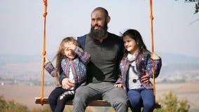 Portrait de papa balançant avec des filles sur une oscillation sous un arbre banque de vidéos