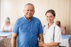 Portrait de patient masculin supérieur de sourire avec le docteur féminin Images stock