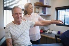 Portrait de patient masculin supérieur de sourire présentant la main de examen de docteur féminin Photo stock