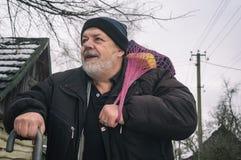 Portrait de paysan plus âgé positif avec le bâton de marche portant une certaine substance dans le sac ficelé Photographie stock