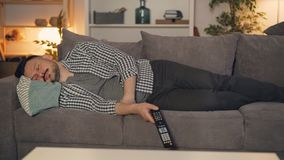 Portrait de personne fatiguée dormant sur le divan seule TV se tenante à télécommande clips vidéos