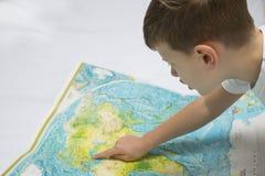 Portrait de petit garçon étudiant la carte du monde images libres de droits