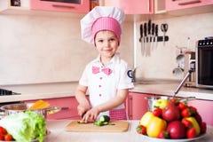 Portrait de petit garçon dans le chapeau du chef et d'un tablier Petits cuisiniers de chef dans la cuisine Portrait de garçon mig Photographie stock libre de droits