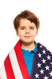 Portrait de petit garçon enveloppé dans le drapeau des Etats-Unis Photo libre de droits