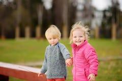 Portrait de petit garçon et de fille jouant sur l'arrière cour de jardin d'enfants Images stock