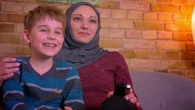 Portrait de petit garçon et sa de mère musulmane dans l'éclat de hijab riant la comédie de observation à la TV à la maison banque de vidéos