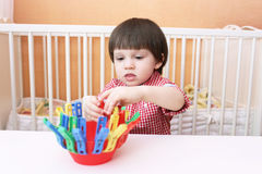 Portrait de petit garçon jouant avec des pinces à linge Photo libre de droits