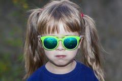 Portrait de petite fille à la mode dans des lunettes de soleil vertes dehors Photo libre de droits