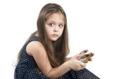 Portrait de petite fille aux yeux bleus avec le téléphone portable à disposition Images libres de droits