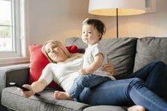 Portrait de petite fille avec la mère sur le salon regardant la TV photo libre de droits