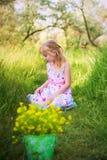Portrait de petite fille avec un seau de fleurs Photographie stock libre de droits