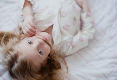 Portrait de petite fille blonde dans des pyjamas roses faisant la moustache hors de ses cheveux et sourire Photo stock