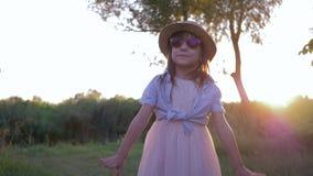 Portrait de petite fille dans les lunettes de soleil et la danse de chapeau de paille à l'appareil-photo au coucher du soleil dan banque de vidéos