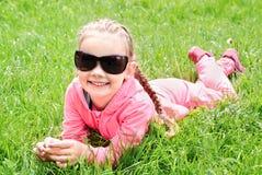 Portrait de petite fille de sourire adorable dans des lunettes de soleil se trouvant dessus Images libres de droits