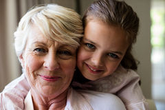 Portrait de petite-fille embrassant sa grand-mère Photos libres de droits