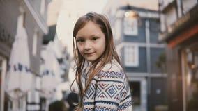 Portrait de petite fille européenne 5-7 années Posant à l'appareil-photo souriant, longs cheveux étonnants Vieux fond de maisons  banque de vidéos