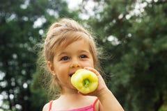 Portrait de petite fille mangeant du poivre extérieur Photo stock