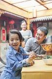 Portrait de petite fille mangeant le dîner avec sa famille Photographie stock libre de droits
