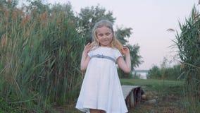 Portrait de petite fille mignonne avec des yeux bleus dans le chapeau de paille et la robe blanche en nature parmi de hauts rosea banque de vidéos