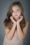 Portrait de petite fille mignonne avec les mains pliées près du visage Photo stock