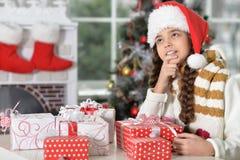 Portrait de petite fille mignonne dans le chapeau de Santa avec des cadeaux pour Noël photographie stock