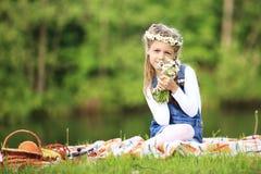 Portrait de petite fille mignonne dans une guirlande et un bouquet de wildfl Images libres de droits