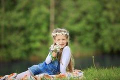 Portrait de petite fille mignonne dans une guirlande et un bouquet de wildfl Photo stock