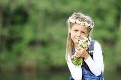 Portrait de petite fille mignonne dans une guirlande et un bouquet de wildfl Photographie stock