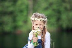 Portrait de petite fille mignonne dans une guirlande et un bouquet de wildfl Images stock