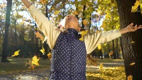 Portrait de petite fille sautant et jetant les feuilles jaunes en parc d'automne clips vidéos