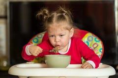 Portrait de petite fille soufflant sur le gruau chaud pour refroidir la séance dans la chaise d'alimentation photographie stock