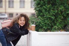 Portrait de petite fille de sourire bouclée de hippie dans la veste avec du café Type urbain Automne extérieur Photographie stock