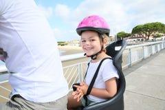 Portrait de petite fille sur la bicyclette du père Photo stock