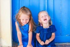Portrait de petites filles de sourire s'asseyant près de vieux Photographie stock