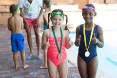 Portrait de petites filles montrant des pouces au poolside photos libres de droits