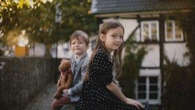 Portrait de petits garçon et fille européens Le frère et la soeur s'asseyent ensemble regardant l'appareil-photo Demi maisons de  clips vidéos