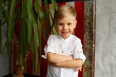 Portrait de peu de joli garçon souriant au-dessus de drapeau américain comme backg Images stock