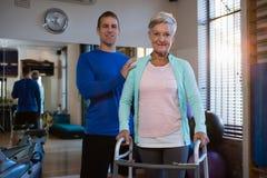 Portrait de physiothérapeute et de patient sur le cadre de marche Image stock