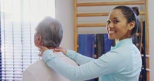 Portrait de physiothérapeute heureux donnant le massage de cou au patient supérieur 4k clips vidéos
